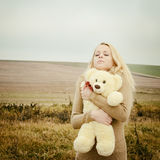 Young sensual girl blonde in windy fall with toy Royalty Free Stock Photography