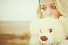Young sensual girl blonde in windy fall with toy Royalty Free Stock Photos