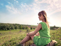 Young sensual girl sits in a grass outdoors Royalty Free Stock Photography