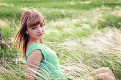 Young sensual girl sits in a grass outdoors Royalty Free Stock Photos