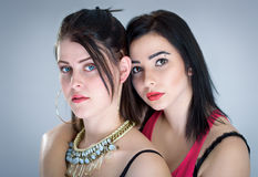 Young sensual girls. Studio portrait of two sensual girls isolated on grey background Royalty Free Stock Photo