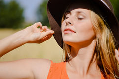 Young sensual lady wearing hat exposing her face. Beautiful young lady wearing hat touching it with her hand exposing her face to sun on hot sunny day, close up Stock Photos