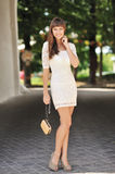 Young sensual lady in white dress with handbag Stock Photo