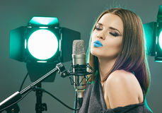 Young sensual model singing into a microphone. Beauty woman Royalty Free Stock Photo
