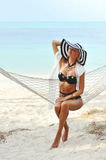 Young sensual model woman portrait relaxing in hammock on a beac Stock Photography