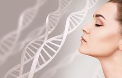 Portrait of sensual woman among DNA chains. Young sensual woman among DNA chains over gray background. Biochemistry skin concept royalty free stock image