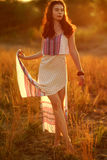 Beautiful girl in a light dress at sunset. Stock Photography