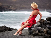Young sensual woman posing on volcanic beach in summer. Young sensual woman posing on black volcanic beach in summer Royalty Free Stock Photo