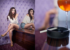 Young sensual woman siting alone smoking in a modern night club Stock Photography