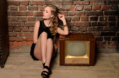 Young sensual woman sitting near retro tv set. Young sensual woman sitting on floor near retro tv set on old brick wall background Royalty Free Stock Photo