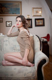 Young sensual woman sitting on sofa relaxing. Beautiful long hair girl with comfortable clothes daydreaming on the couch, alone Royalty Free Stock Photography