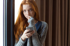 Young sensual woman touching her lips and using smartphone. Young sensual redhead young woman standing near the window, touching her lips and using smartphone Stock Photos