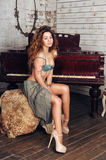 Young sensual young woman in lingerie posing against the grand piano Royalty Free Stock Image