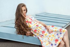 Young sensuality long haired blonde model in cute dress. Sit and looking at camera, blue background Royalty Free Stock Images