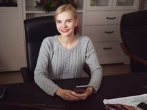 Young serious adorable blonde business lady posing in home office room sitting at the desk with notebook holding mobile phone. Young serious adorable blonde stock images