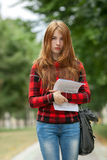 Young serious adorable redhead student woman in red plaid jacket holding her papers posing outdoors on park path with blurred gree. Young serious adorable Royalty Free Stock Images