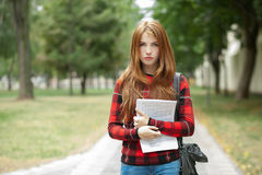 Young serious adorable redhead student woman in red plaid jacket holding her papers posing outdoors on park path with blurred gree Stock Photography