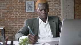 Young serious african american businessman writing notes from laptop and sitting in modern office, concentrated and stock video footage