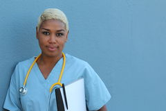Young serious afro american nurse standing at hospital ward with clipboard and pen in hand. Neutral expression, looking at camera Stock Photos