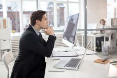 Young serious analyst. Serious young businessman sitting by his desk and concentrating on financial analysis royalty free stock photography