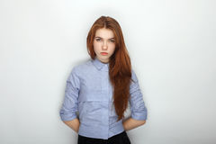 Young serious angry redhead beautiful woman in shirt portrait on a white background hidden hands Royalty Free Stock Photo