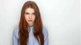 Young serious angry redhead beautiful woman in shirt portrait on a white background Stock Photography