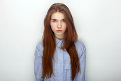 Young serious angry redhead beautiful woman in shirt portrait on a white background Stock Images