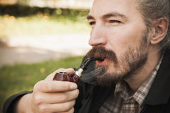 Young serious asian bearded man smokes. Young serious asian bearded man smoking pipe in summer park, close up portrait Royalty Free Stock Image