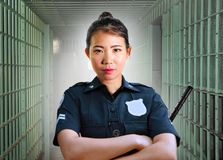 Young serious and attractive Asian Korean guard woman standing on cell at State penitentiary wearing police uniform in crime stock photography
