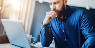 Young bearded businessman sitting in front of computer, looking at screen, holding pen, thinking. Freelancer works home. Stock Photos