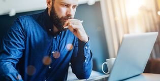 Young bearded businessman sitting in front of computer, looking at screen, holding pen, thinking. Freelancer works home. Stock Images