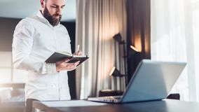 Young serious bearded businessman stands near desk opposite laptop and makes notes in notebook. Student is studying stock photo