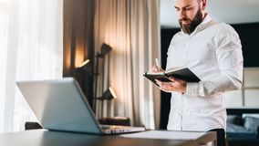 Young serious bearded businessman stands near desk opposite laptop and makes notes in notebook. Student is studying royalty free stock photography