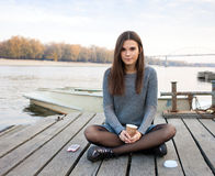 Young Serious Beautful Brunette Woman With Her Smartphone Outdoors Royalty Free Stock Photography