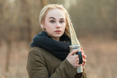 Young serious beautiful blonde hipster woman posing with thermos cup cold season outdoors Stock Photos