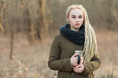 Young serious beautiful blonde hipster woman posing with thermos cup cold season outdoors Stock Photo