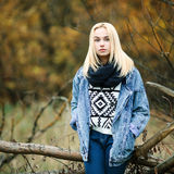 Young serious beautiful blonde woman in jeans, scarf, and sweater, posing in autumn background Stock Photo