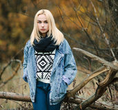 Young serious beautiful blonde woman in jeans, scarf, and sweater, posing in autumn background Stock Photos