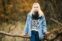 Young serious beautiful blonde woman in jeans, scarf, and sweater, posing in autumn background Royalty Free Stock Photos