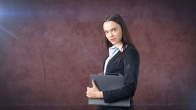 Young serious beautiful businesswoman portrait with gray briefcase, dark background Stock Image