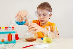 Young serious boy in safety goggles studies chemical practice in laboratory Stock Photography