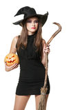 The  young serious brunette witch with a broom Stock Photo