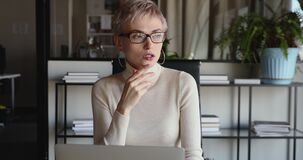 Young serious business woman thinking of business challenge using laptop