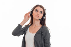 Young serious business woman in uniform with headphones and microphone looking away isolated on white background Royalty Free Stock Photo