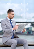 Young serious businessman newspaper outdoors Royalty Free Stock Photo