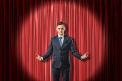 Young serious businessman with palms up on red stage curtains background royalty free stock photo