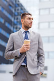 Young serious businessman with paper cup outdoors Royalty Free Stock Photos