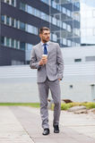 Young serious businessman with paper cup outdoors Royalty Free Stock Images