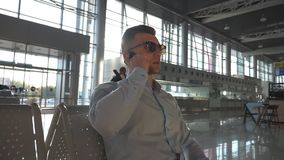 Young serious businessman talking on phone at airport. Close up portrait of handsome caucasian business man in stock video
