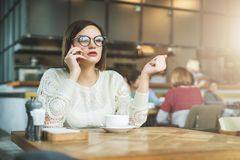 Young serious businesswoman in glasses sitting in cafe at wooden table and talking on cell phone. Telephone conversations. Hipster girl freelancer discusses Royalty Free Stock Photo